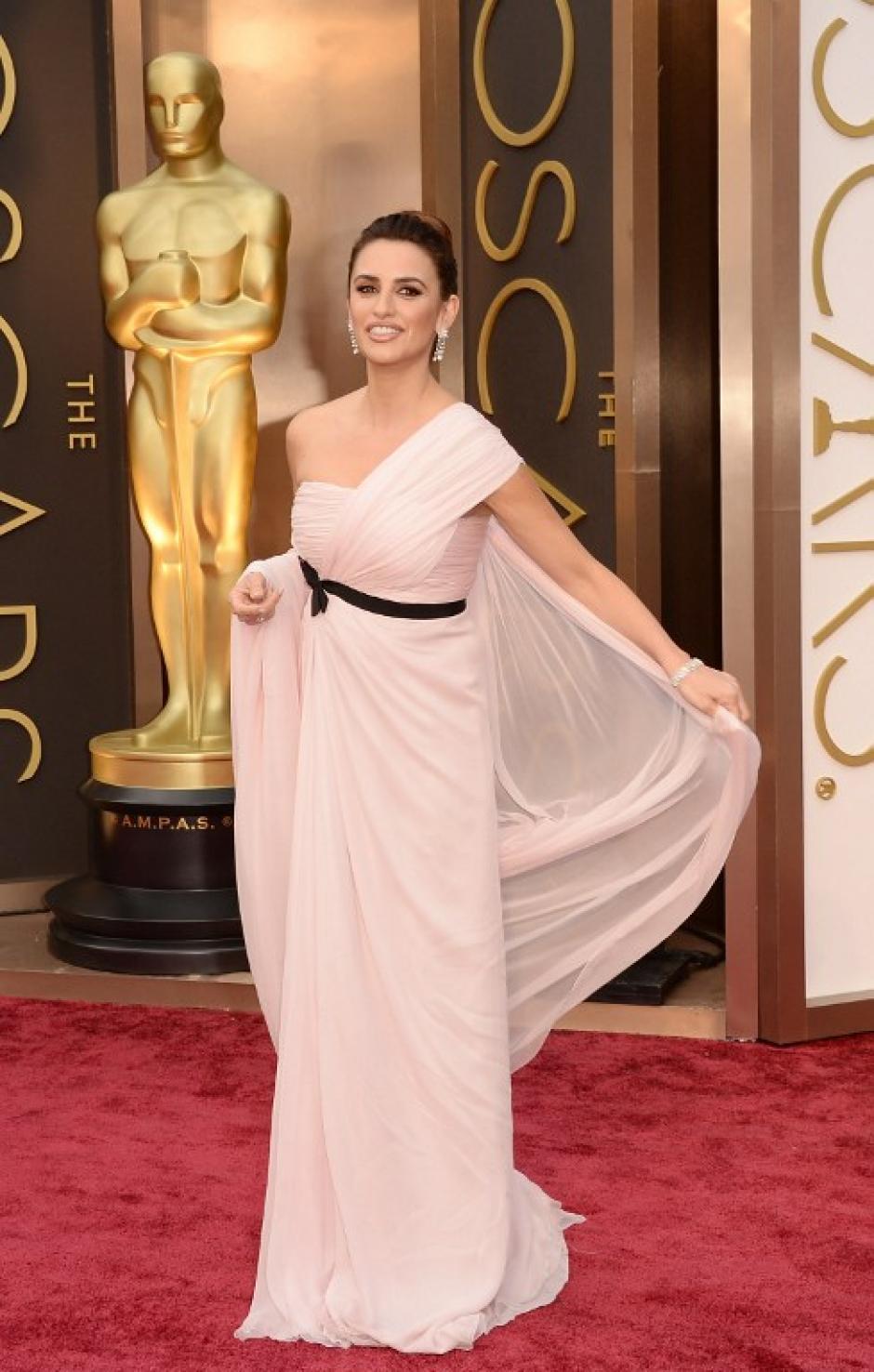 Penélope Cruz muy elegante con un peinado recogido, aretes largos de diamantes y un vestido rosado con detalle en negro. (Foto: AFP)