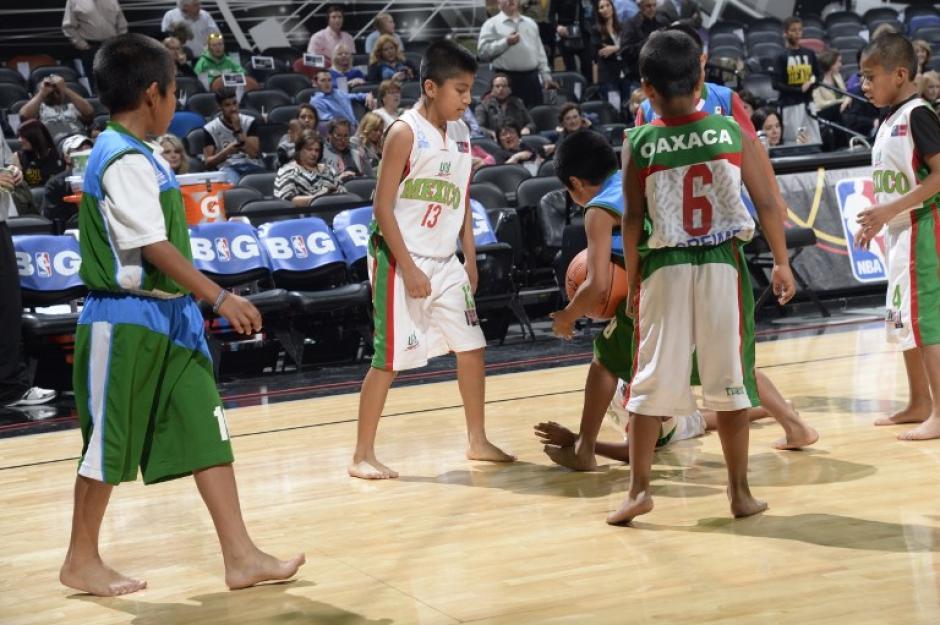 """Los niños """"Triquis"""", originarios de Oaxaca, México, y famosos por jugar baloncesto descalzos, fueron invitados por segunda vez a la duela de los Spurs de San Antonio y jugaron entre sí al medio tiempo del juego entre los Spurs y los Heat. (Foto: AFP)"""