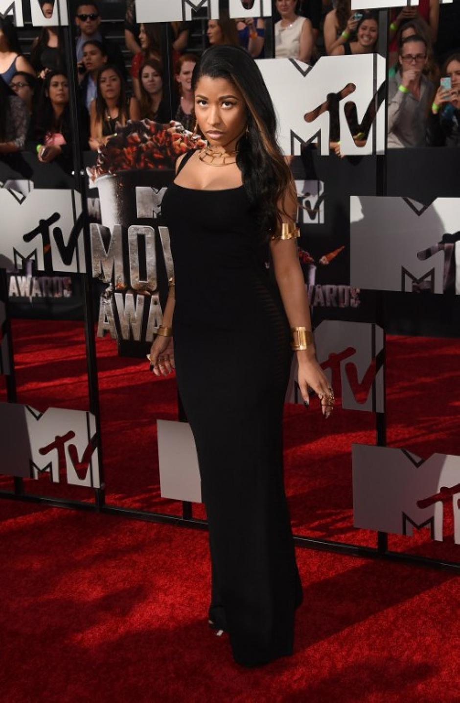 A diferencia de otras veces cuando destaca por sus exóticos atuendos, la artista Nicki Minaj se enfundó en un sobrio vestido negro en premios MTV. (Foto:AFP)