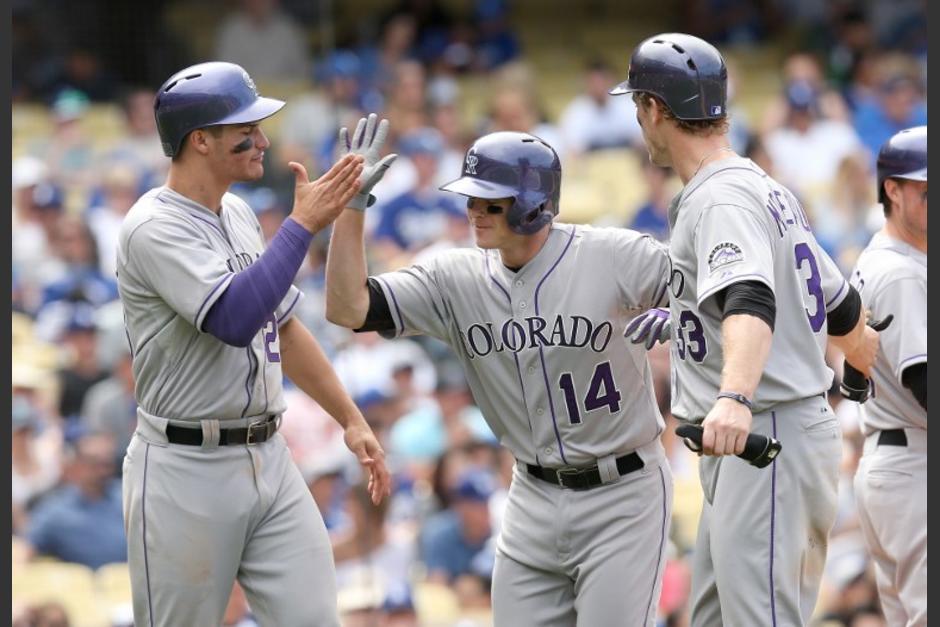 Josh Rutledge (14) y Nolan Arenado (28) celebran la fictoria ante los Dodgers