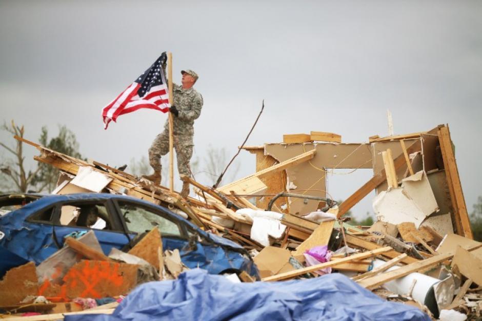 El sargento de la Guardia Nacional de Arkansas, Skipper Smith cuelga una bandera americana en una casa que detruida cuando un tornado azotó la zona de Vilonia, Arkansas. Los tornados azotaron la región 27 de abril, dejando a más de una docena de muertos. (Foto: Mark Wilson / AFP)
