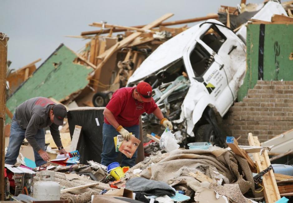 Gary Moore levanta unas revistas de los escombros de su casa, donde una vez estuvo antes de ser destruida por un tornado. (Foto: Mark Wilson/ AFP)