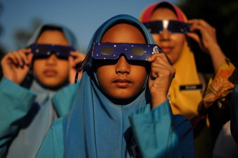Un grupo de estudiantes de Malasia se preparan con lentes para observar el eclipse que ocurrió hace una horas y pudo ser visible en el continente asiático. (Foto: AFP)