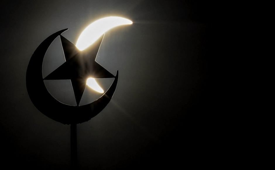 Una vista general muestra un eclipse parcial de sol detrás de un símbolo de la estrella y la media luna encima de una mezquita en Kuala Lumpur. (Foto: AFP)