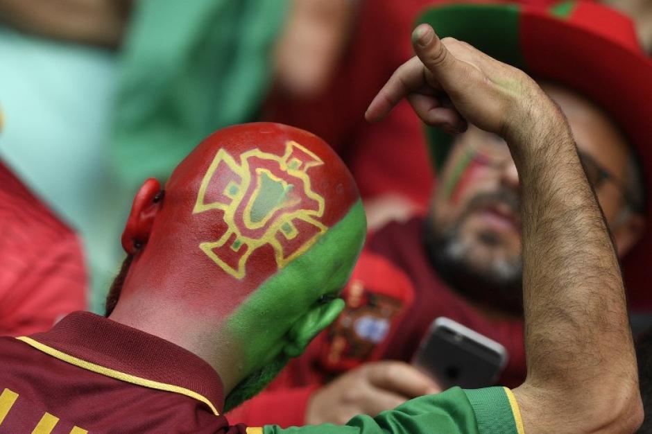 Y algunos suelen ser más detallistas como este que se pinta el escudo de Portugal que clasificó a Octavos de final. (Foto: AFP/MARTIN BUREAU)