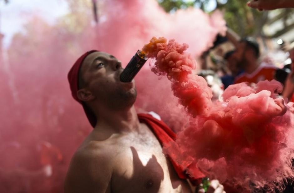 Un aficionado Gales coloca una bomba de humo en su boca sin medir los riesgos que esto representa en la ciudad de Toulouse. (Foto: AFP/BULENT KILIC)
