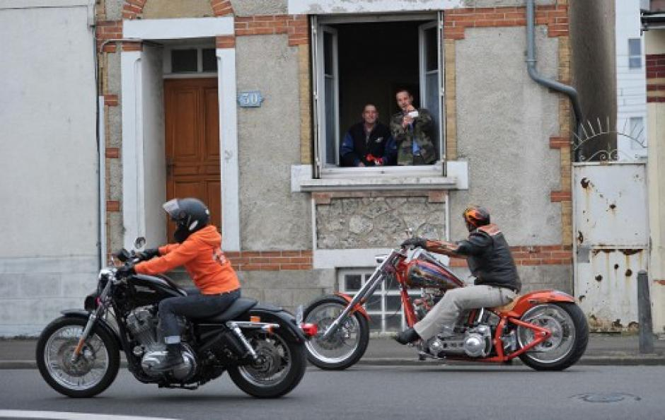 Varios vecinos de la ciudad de Tours toman fotografías a los motociclistas. (Foto: Guillaume Souvant/AFP)