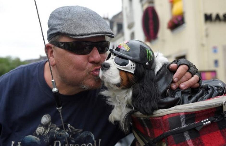 Un hombre le da un beso a su mascota previo a partir en la caravana del desfile motorizado. (Foto: Guillaume Souvant/AFP)
