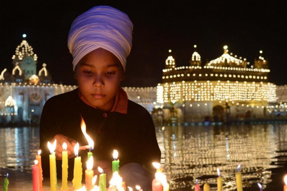 Un indio sij devoto enciende velas en el sagrado Templo Dorado, santuario del sijismo iluminado en Amritsar, en vísperas de Bandi Chhor Divas o Diwali. Los Sijs celebran con motivo del regreso de la Sexta Guru, Guru Hargobind Ji, quien fue liberado de la prisión y también logró liberar a 52 presos políticos.