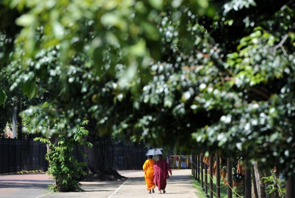 """En Sri Lanka, dos monjes budistas caminan más allá del """"Templo del Diente"""" en la ciudad central de Kandy, tomada el 20 de noviembre de 2013. El santuario, declarado Patrimonio Mundial de la UNESCO, es uno de los lugares más importantes de adoración de la mayoría budista de la isla. (LAKRUWAN WANNIARACHCHI/AFP)"""