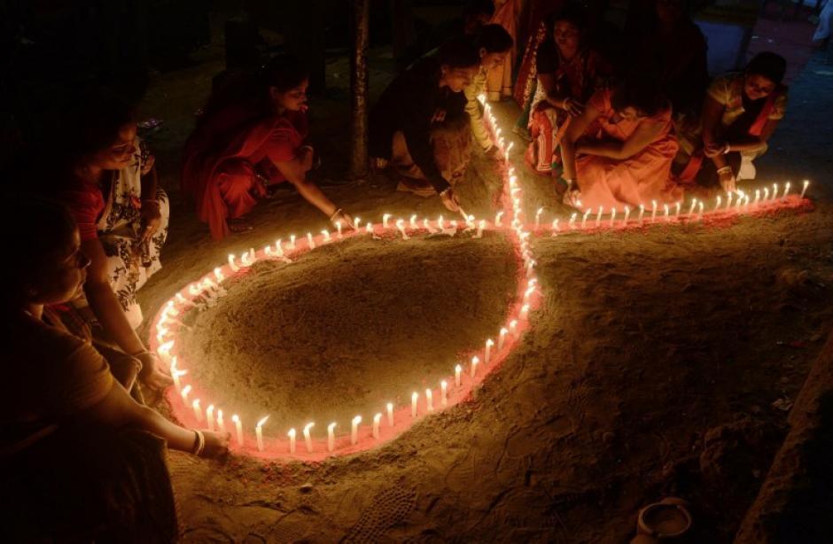"""Voluntarios de la India y miembros de la Asociación Voluntaria de Salud de Bengala Occidental (WBVHA en sus siglas en ingles) encienden velas con la forma de una cinta roja durante la ceremonia de clausura de una campaña de sensibilización sobre el SIDA con motivo del 'Día Mundial del SIDA """"en la imagen del 2 de diciembre tomada por el fotógrafo de AFP Diptendu Dutta."""