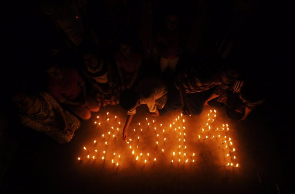Escolares indios encienden velas formando la fecha '2014 'en una escuela en Agartala el 30 de diciembre de 2013, un día antes de las celebraciones de Año Nuevo. Personas en todo el mundo se están preparando para recibir a 2014. AFP PHOTO / ARINDAM DEY