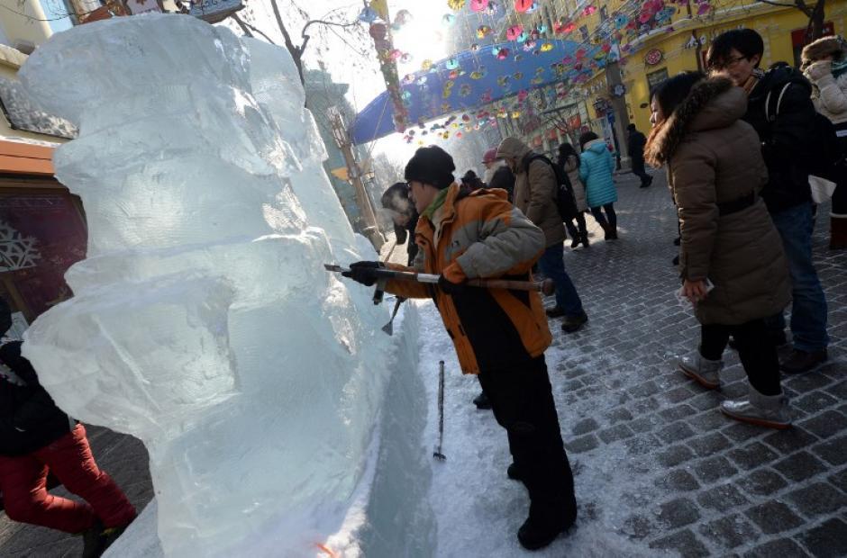 Escultores de hielo trabajan en su creación a lo largo de una calle en el de China Ice and Snow World, de la 15 ª Festival Internacional de Hielo y Nieve de Harbin, provincia nororiental china de Heilongjiang, el 4 de enero de 2014. AFP PHOTO / GOH CHAI HIN