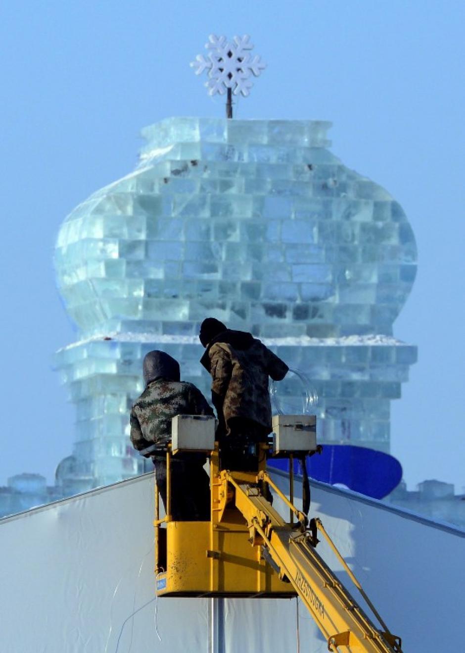 """Los trabajadores hacen preparativos de último minuto en el China Ice and Snow World, para la ceremonia de apertura del 15 º Festival Internacional de Hielo y Nieve de Harbin, provincia nororiental china de Heilongjiang el 4 de enero de 2014. """"Hielo y Nieve del Mundo"""" de este año se abre el 5 de enero, la voluntad cuenta el tema """"Ice Global y Snow Dream, Información Cartoon World"""". AFP PHOTO / GOH CHAI HIN"""
