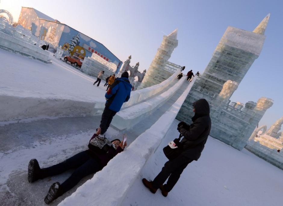 Los visitantes disfrutan de las diapositivas en una escultura de hielo en el Hielo China y Snow World y hacen preparativos de último minuto para la ceremonia de apertura del 15º Festival Internacional de Hielo y Nieve de Harbin, provincia nororiental china de Heilongjiang el 4 de enero de 2014. AFP PHOTO / GOH CHAI HIN
