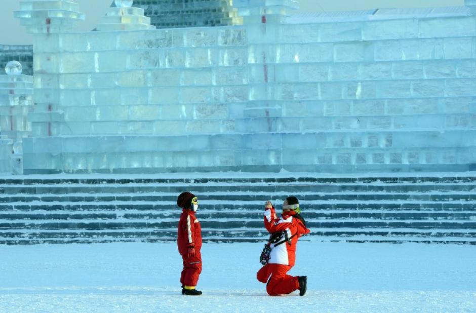 Una mujer toma una fotografía de su hijo en su visita a una escultura de hielo en el China Hielo y Nieve del Mundo; esta es una atracción en el país y se celebra durante el inicio de año.AFP PHOTO / GOH CHAI HIN