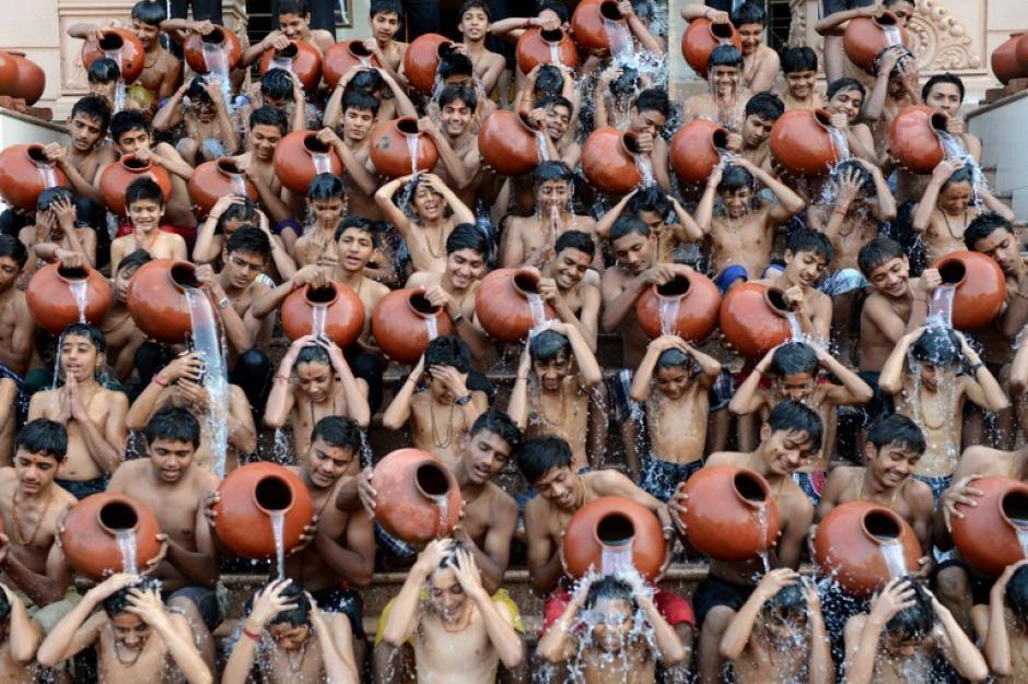 """Estudiantes de la India participan en el """"baño sagrado"""" en Ahmedabad. La tradición señala que deben darse un baño diario matinal con agua fría para purificar el cuerpo. Foto AFP"""
