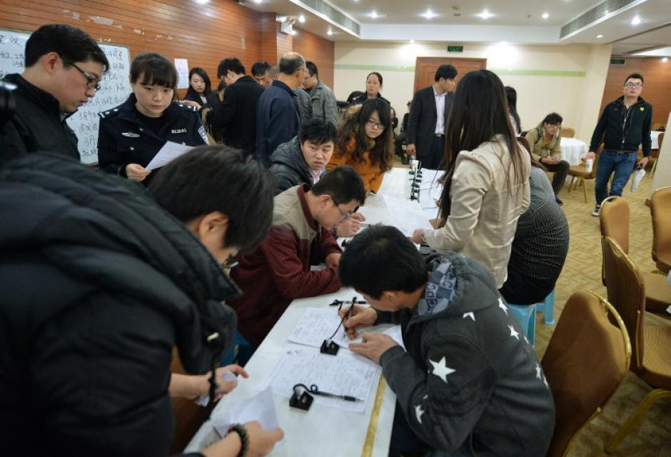 Familiares chinos de los pasajeros desaparecidos llenan formularios para poder viajar a Malasia si encuentran al avión dentro de ese territorio