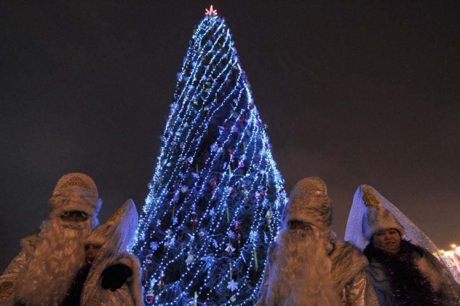 Gente vestida como el Papá Noel ruso, Ded Moroz (Abuelo Frost) y su compañero Snegurochka (Snow Maiden) se colocan cerca de un árbol de Año Nuevo, en el centro de Ala-Too Square, en la capital de Kirguistán. (Foto: AFP)