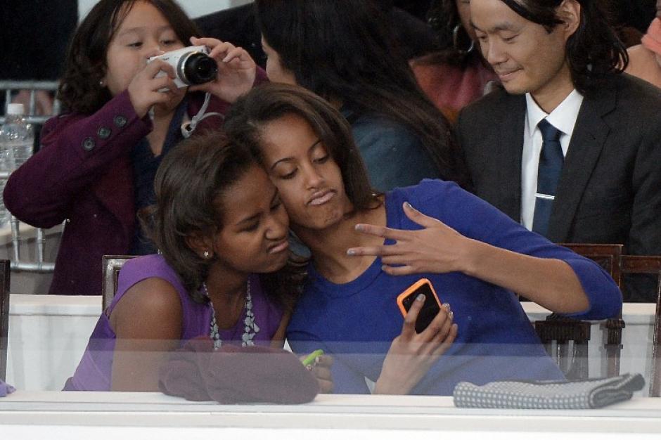 Sasha (L) y Malia Obama, las hijas del presidente de EE.UU., Barack Obama, toman una foto de sí mismas durante el Desfile Inaugural Presidencial el 21 de enero de 2013, de Washington, DC.(Foto: AFP/JOE KLAMAR)