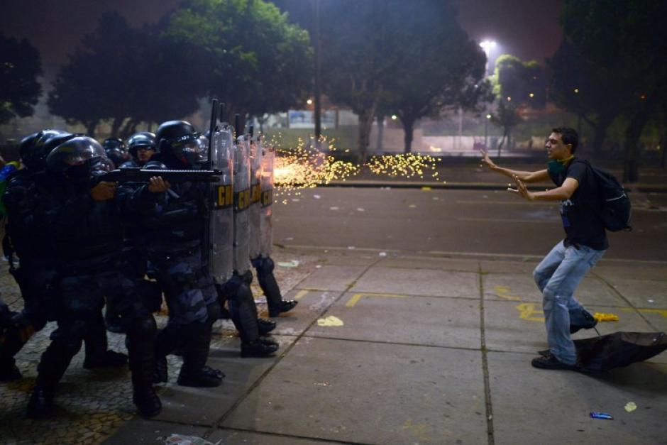 Un manifestante recibe los disparos con balas de goma de oficiales de policía durante una protesta contra la corrupción y la subida de los precios, el 20 de junio de 2013, en Río de Janeiro. (Foto:AFP / CHRISTOPHE SIMON)