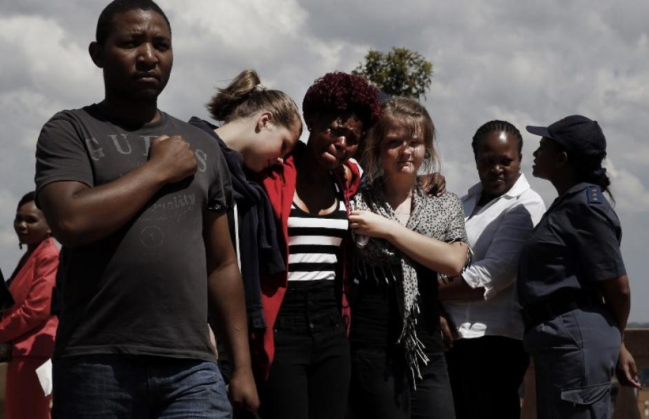 Ciudadanos sudafricanos se consuelan entre sí ante las últimas horas de despedida de su líder Nelson Mandela. Foto AFP