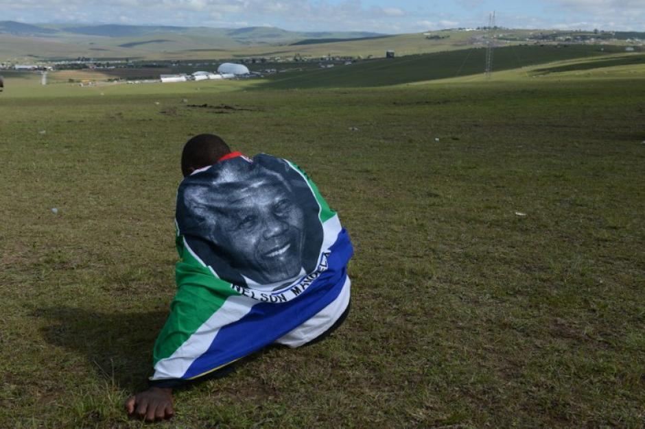 Un hombre envuelto en una bandera de Sudáfrica se sienta en una colina para decir adiós a Nelson Mandela en Qunu, su pueblo natal. (Foto: AFP)