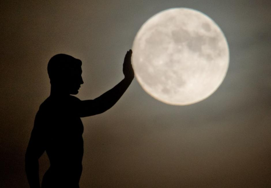 En esta Luna llena tomada desde Hanover, Alemania, una escultura crea una ilusión de cercanía con el satélite natural, en la foto del 17 de diciembre tomada por el fotógrafo Julian Stratenschulte de AFP.