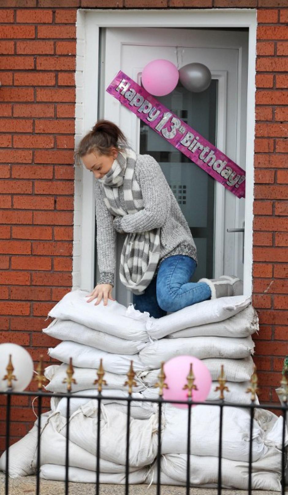 Una mujer trepa sobre sacos de arena apilados en frente de la puerta de su casa. Todos los residentes en esa ciudad se preparan para las inundaciones anunciadas al este de Belfast, Irlanda del Norte. AFP PHOTO / PETER MUHLY