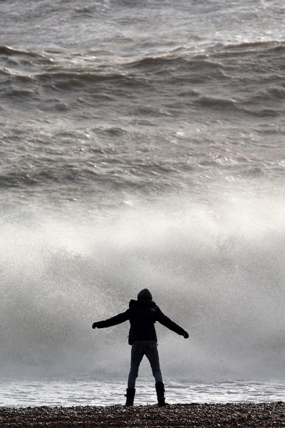 Un joven observa las olas que se estrellan en la playa junto al muelle de Brighton, en el sur de Inglaterra, después de una marea alta. Las autoridades siguen en alerta. AFP PHOTO / CARL COURT