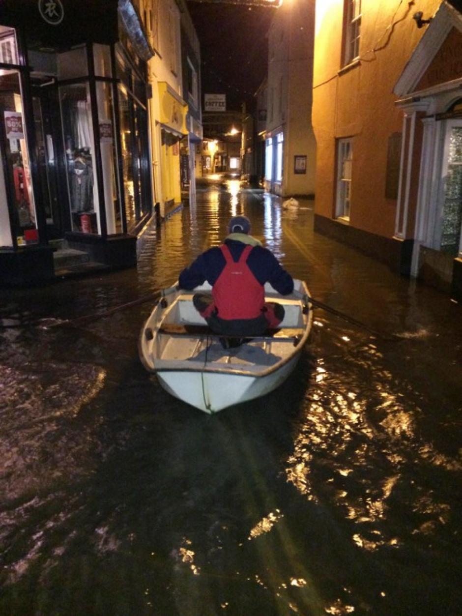 Un hombre rema en una embarcación por la calle principal de Salcombe en Devon, suroeste de Inglaterra. Tormentas y fuertes vientos causaron inundaciones en varias partes de Inglaterra. AFP PHOTO / RNLI