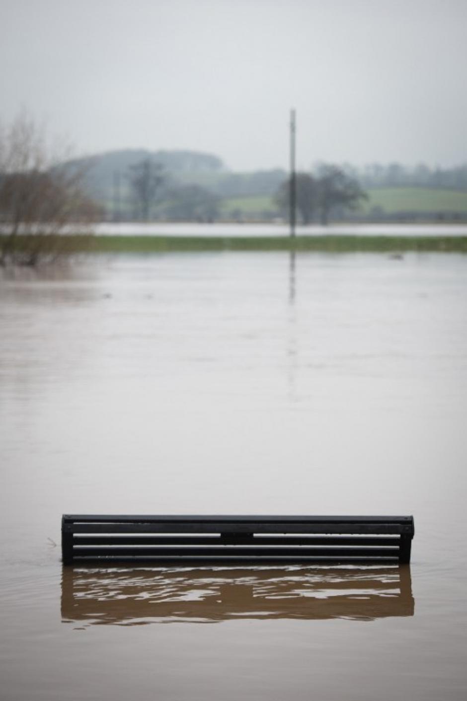 Inglaterra también ha sido afectada por el clima lluvioso. Un banco del parque quedó sumergido por el río Severn en Upton Upon Severn. Los informes meteorológicos indican más tormentas para las próximas 48 horas. AFP PHOTO / LEON NEAL