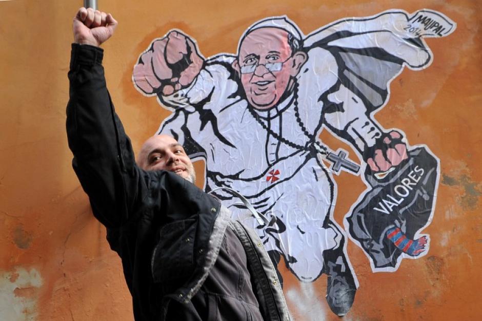 """El artista callejero italiano Maupal posa junto a un mural mostrando al Papa Francisco como un superhombre, volando por el aire con su manto y detrás de él un bolso con la palabra """"Valores"""". La imagen pintada en Roma creada por Maupal fue tuiteada en la cuenta oficial de comunicación del Vaticano @PCCS_VA. Esta es la foto del 29 de enero tomada por la fotógrafa de AFP Tiziana Fabi."""