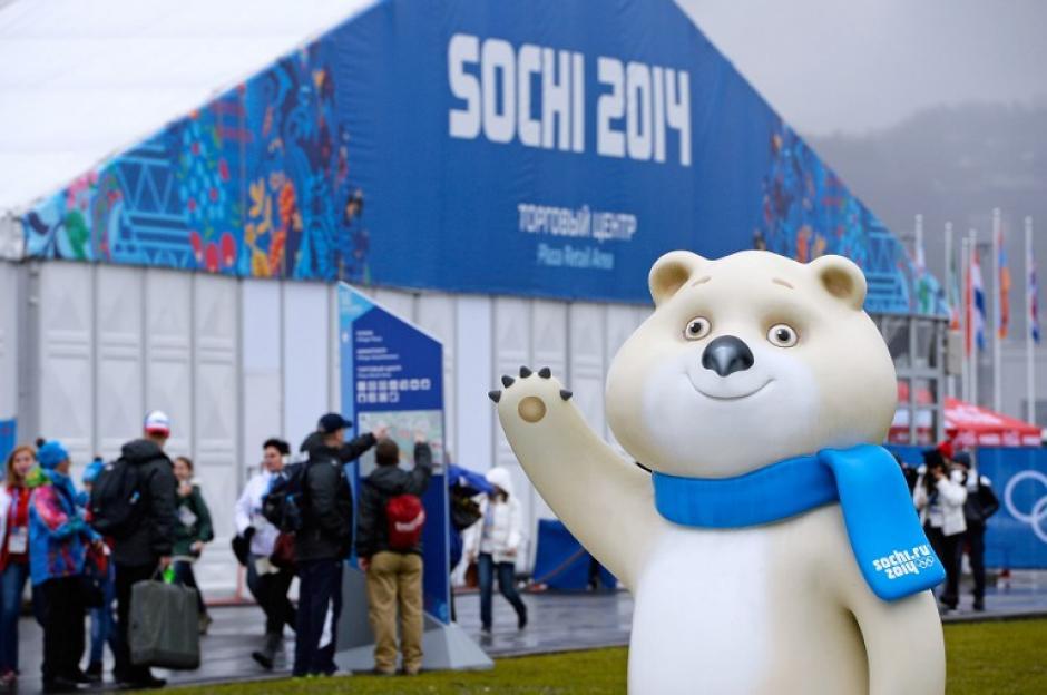 El oso polar, mascota de los Juegos Olímpicos de Sochi saluda, mientras atletas que participarán en la competición, buscan su ubicación en la Villa Olímpica. Foto AFP