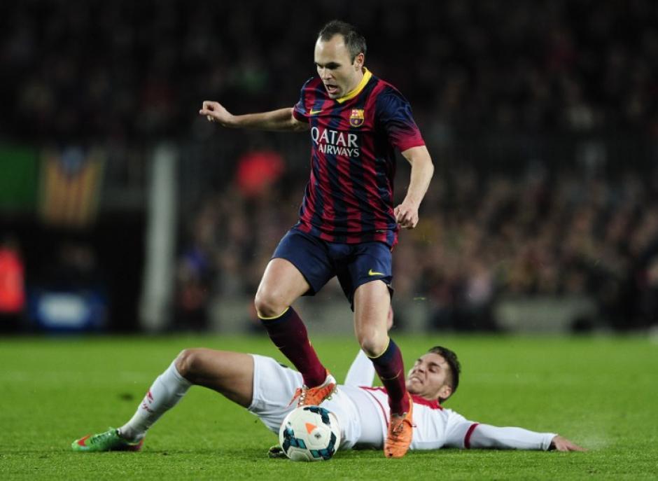 El centro campista del Rayo, Rubén Rochina intenta quitar la pelota a Ándres Iniesta en un partido que terminó con 6 goles a favor del Barcelona.