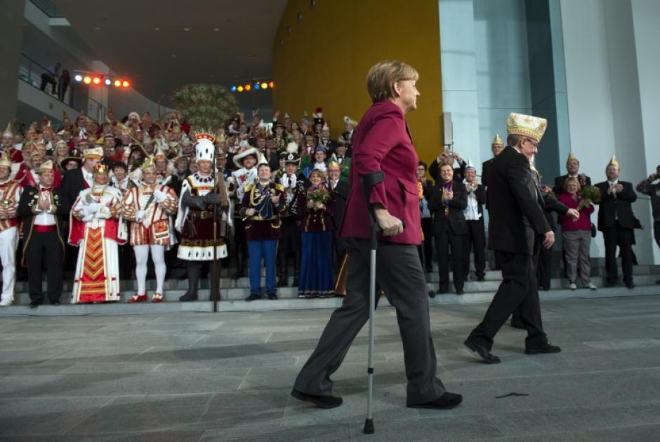 La canciller alemana Angela Merkel camina con muletas frente a aficionados al carnaval, el 18 de febrero de 2014. Merkel recibe cada año a los príncipes y princesas del Carnaval en la Cancillería antes del inicio de la temporada de fiestas (Foto: AFP / JOHANNES EISELE)