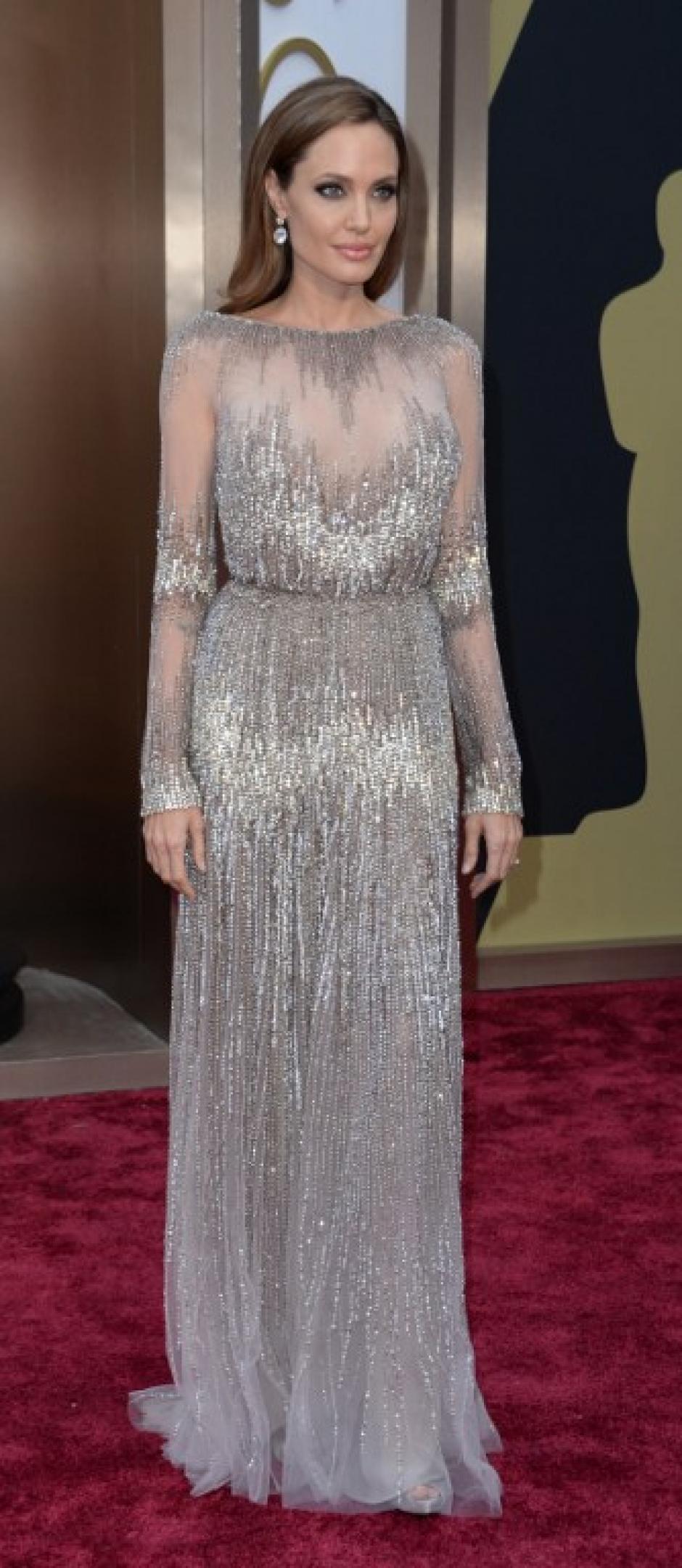 Angelina Jolie llega a la alfombra roja con Brad Pitt. Su vestido es una cascada en tonos plata. (Foto: AFP)