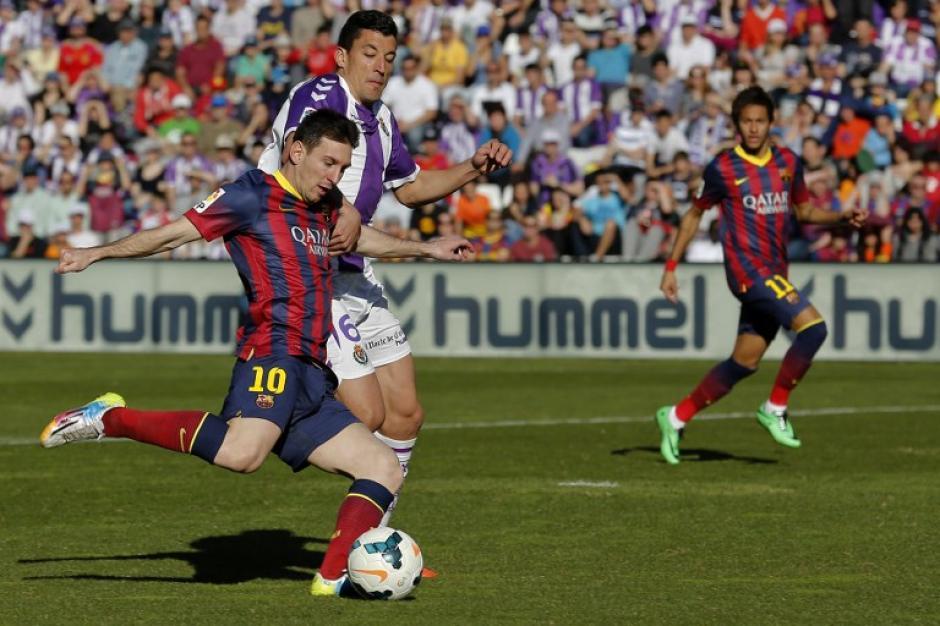 Lionel Messi, delantero del FC Barcelona, trata de desmarcarse de la persecución de Jesús Rueda, defensor del Valladolid. (Foto: AFP)