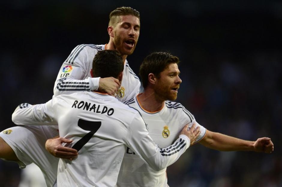 Sergio Ramos y Xabi Alonso felicitan a Cristiano Ronaldo, quien abrió el marcador en el Bernabéu. (Foto: AFP)