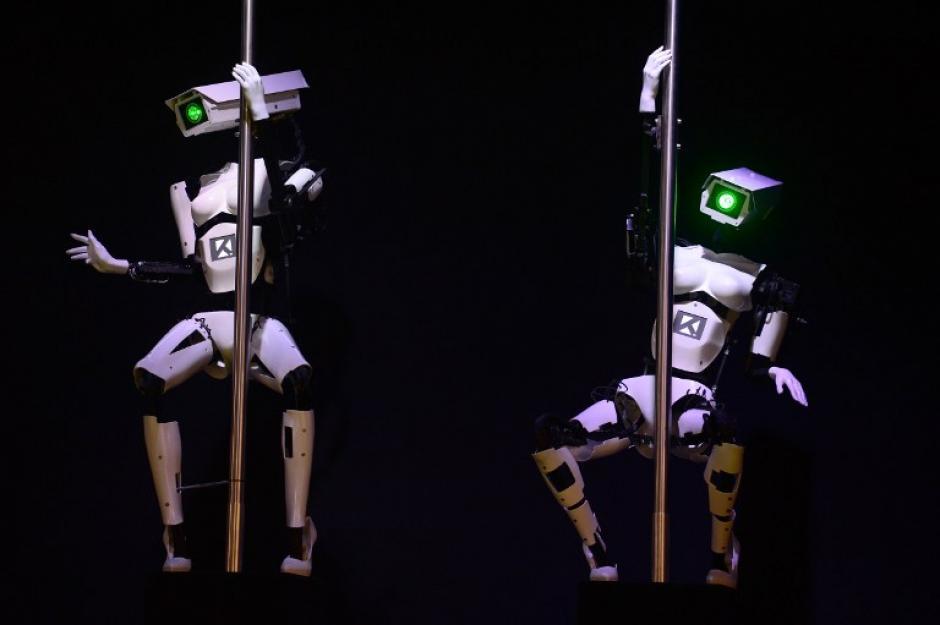"""En la feria de la tecnología CeBIT 2014 que se efectúa en Hannover, Alemania dos robots realizan una """"pole dance"""" o baile del tubo en el stand de la empresa de Software Tobit. (Foto: AFP)"""