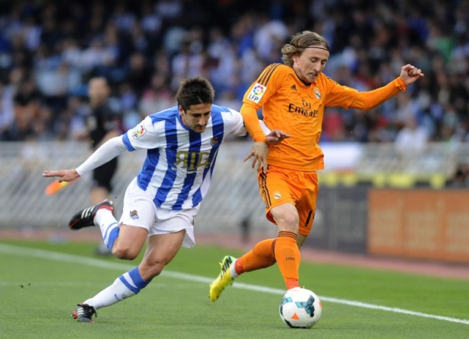 El croata Luka Modric evade al medio campista del Real Sociedad Markel Bergara durante el juego el Real Madrid y el Real Sociedad en Anoeta, el estadio San Sebastián, este sábado. (Foto: AFP)
