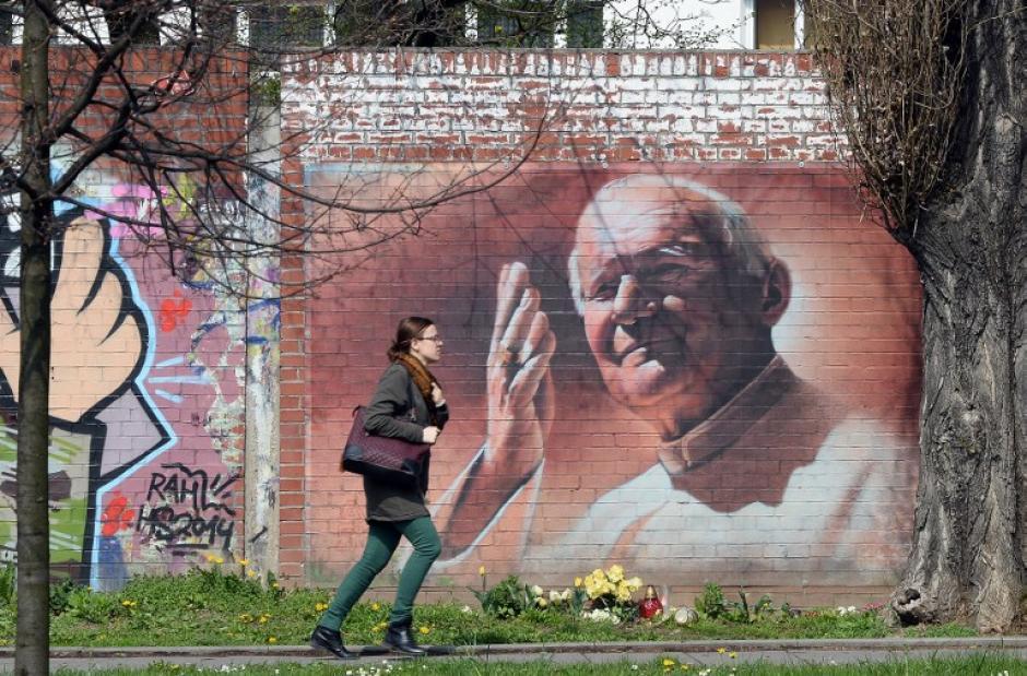 Una joven pasa por un graffiti del Papa Juan Pablo II en Cracovia, Polonia. En Polonia, el fallecido Papa Juan Pablo II es un héroe nacional y autoridad moral, y en su natal Cracovia tiene un museo erigido en su honor. El próximo 27 de abril será canonizado con el Papa Juan XXIII (Foto: AFP)