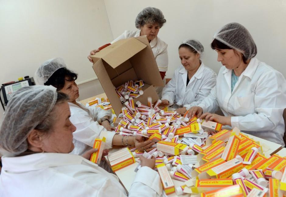 Un grupo de mujeres clasifica los envases de crema de veneno de abeja en la fábrica del Instituto de Investigación y Desarrollo de la Apicultura. (Foto:AFP/DANIEL MIHAILESCU)