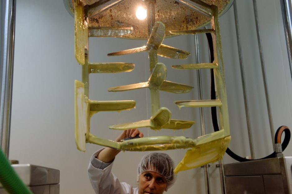 Un trabajador inspeccionan una crema fabricada con veneno de abeja.(Foto: AFP/DANIEL MIHAILESCU)