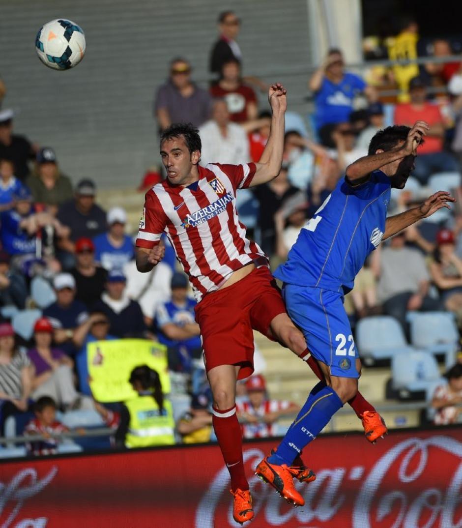 El uruguayo Diego Godín cabecea el balón para anotar, frente al centrocampista del Getafe Juan Antonio Rodríguez. (Foto: AFP/PIERRE-PHILIPPE MARCOU)