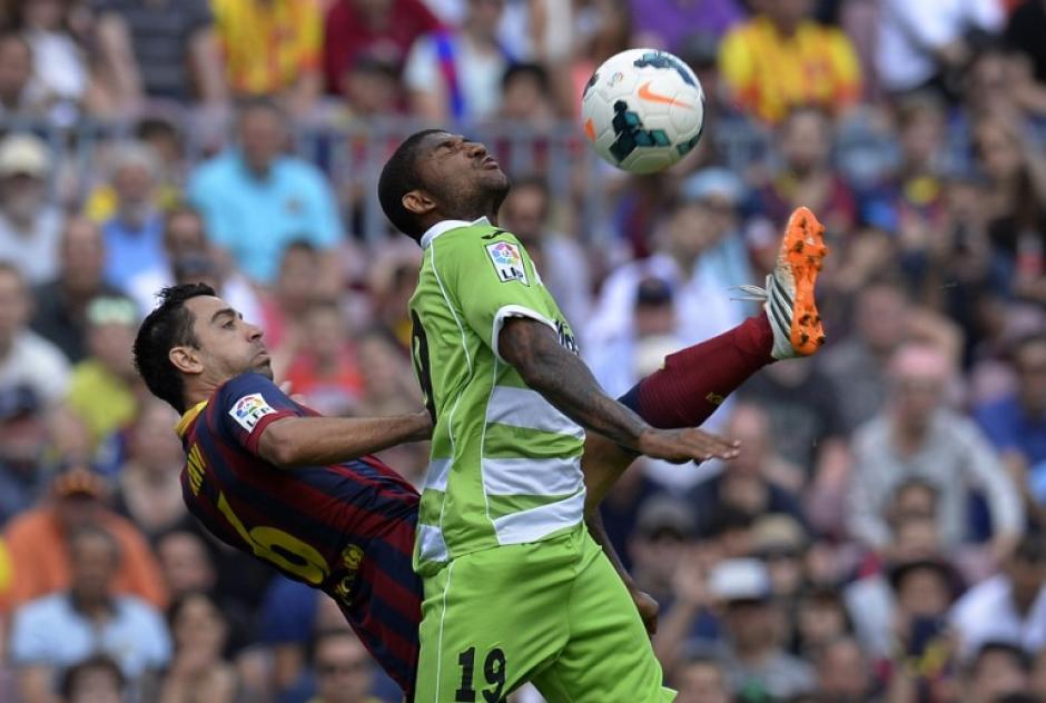 El centrocampista del Barcelona Xavi Hernández disputa la pelota con el defensa del Getafe Sergio Escudero. El partido fue empatado por el equipo del Getafe en tiempo de reposición. (Foto:AFP/LLUIS GENE)