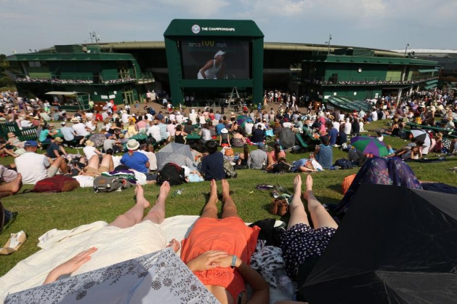 Los aficionados al deporte blanco observan un partido en las pantallas acondicionadas en las afueras delAll England Tennis Club durante el tercer día de competencia. (Foto: AFP/JUSTIN TALLIS)