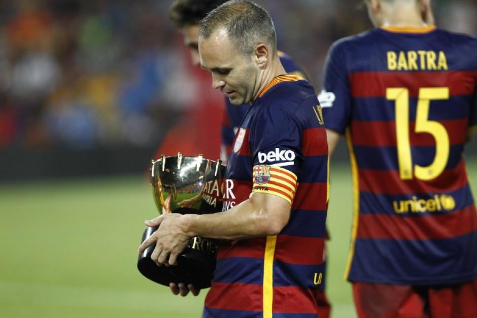 Andrés Iniesta carga en sus brazos el trofeo Joan Gamper
