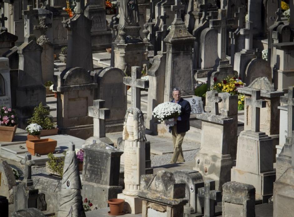Un hombre lleva flores para adornar la tumba de un familiar en un cementerio en Palma de Mallorca el 31 de octubre 2015 en la víspera de Todos los Santos de la Iglesia Católica. (Foto: AFP/ JAIME REINA)