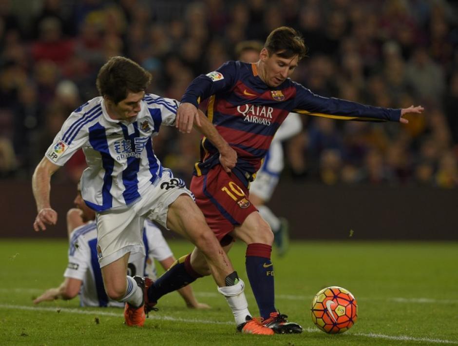 El argentino Lionel Messi (D) hace un regate al mediocampista del Real Sociedad, Gorka Elustondo. (Foto: AFP)